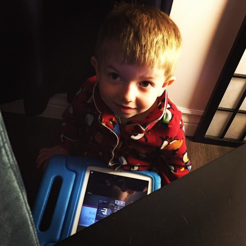 Hiding from Mom with his new iPad.